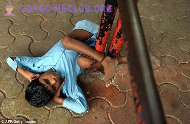 Indian grandmother binds her grandson's legs to the bus stop